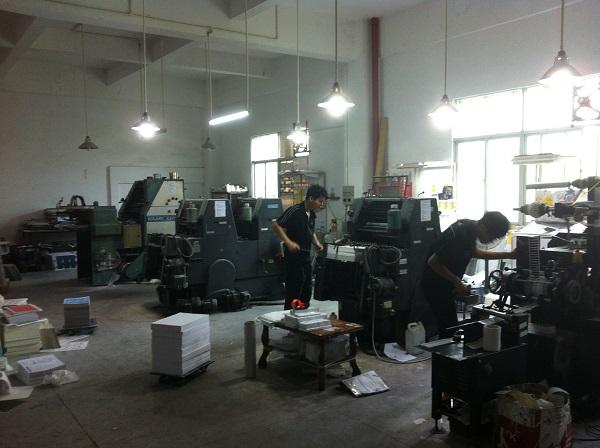 图为印刷厂工人正在操作印刷机器